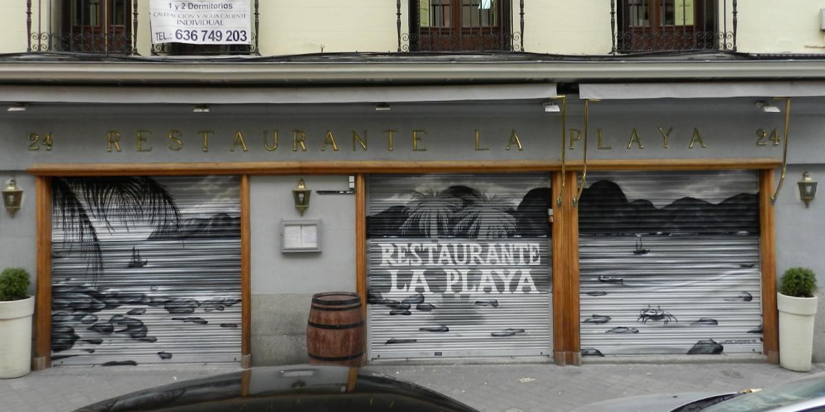 Graffiti en los cierres del restaurante La Playa en Madrid