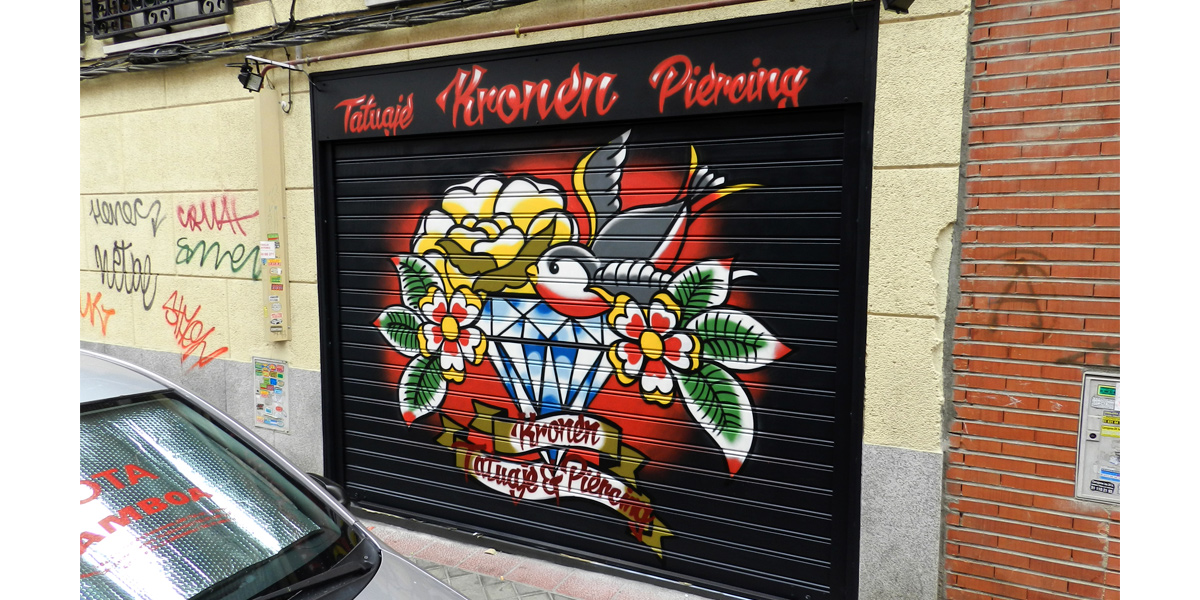 Graffiti en la persiana del estudio de tatuajes Kronen en Vallecas