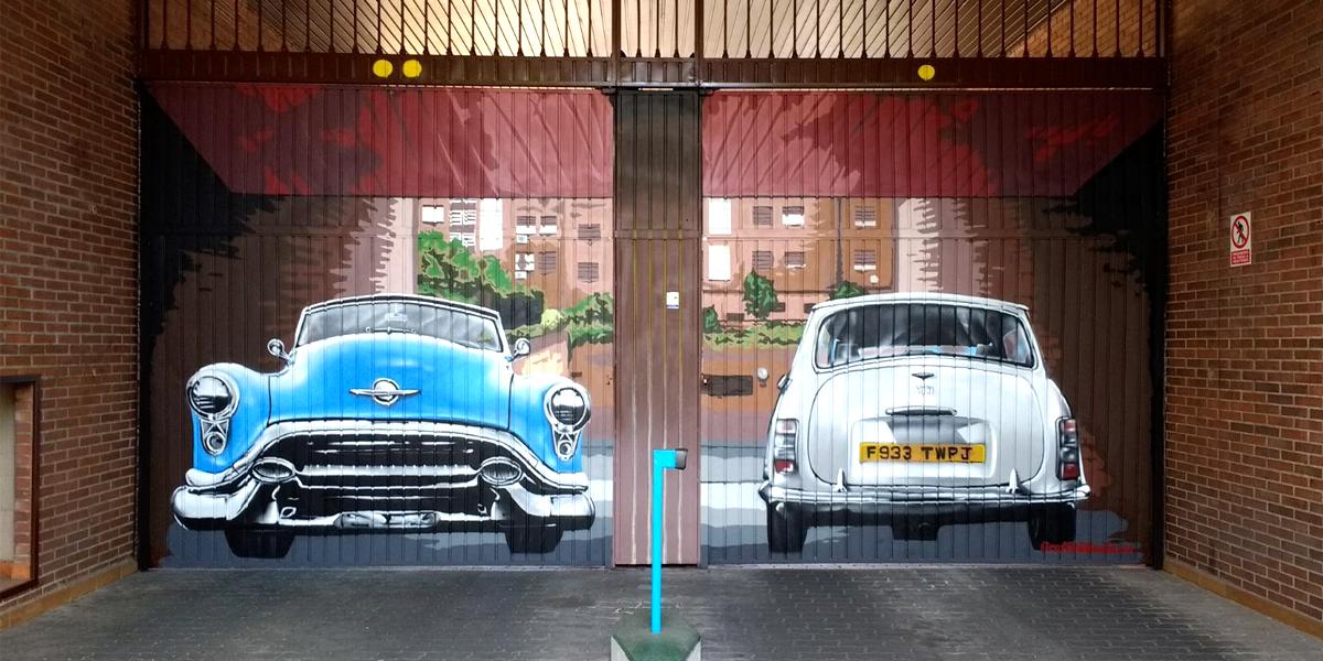Graffiti de coches clásicos en puerta de garaje en Madrid