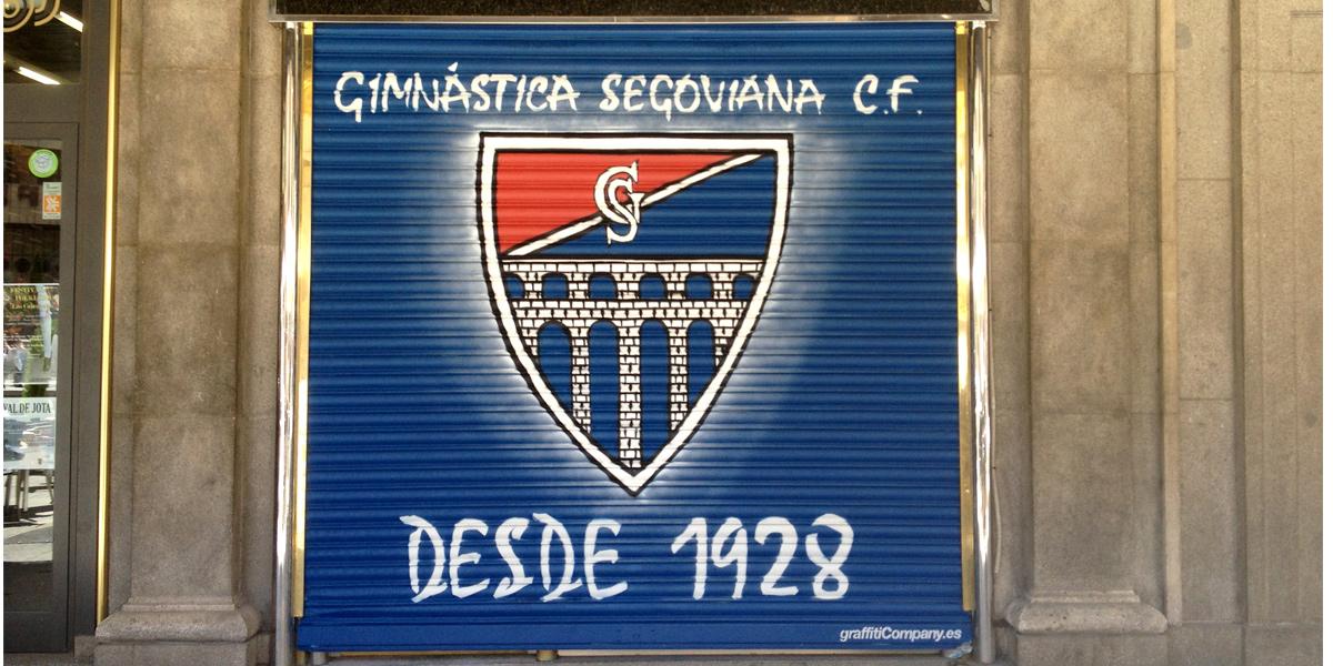 Graffiti en persiana del escudo de la Gimnástica Segoviana en Segovia