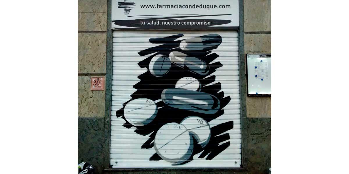 Graffiti en cierre de farmacia de Madrid.