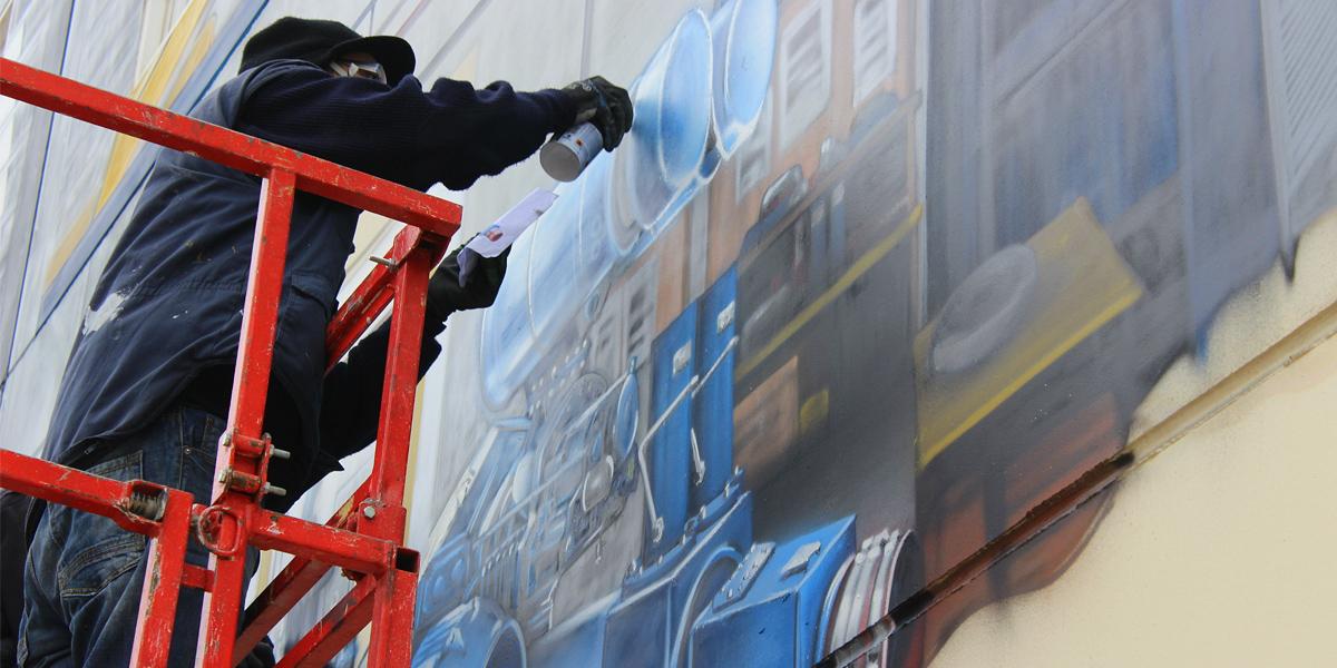 Grafitero pintando trampantojo de gran tamaño