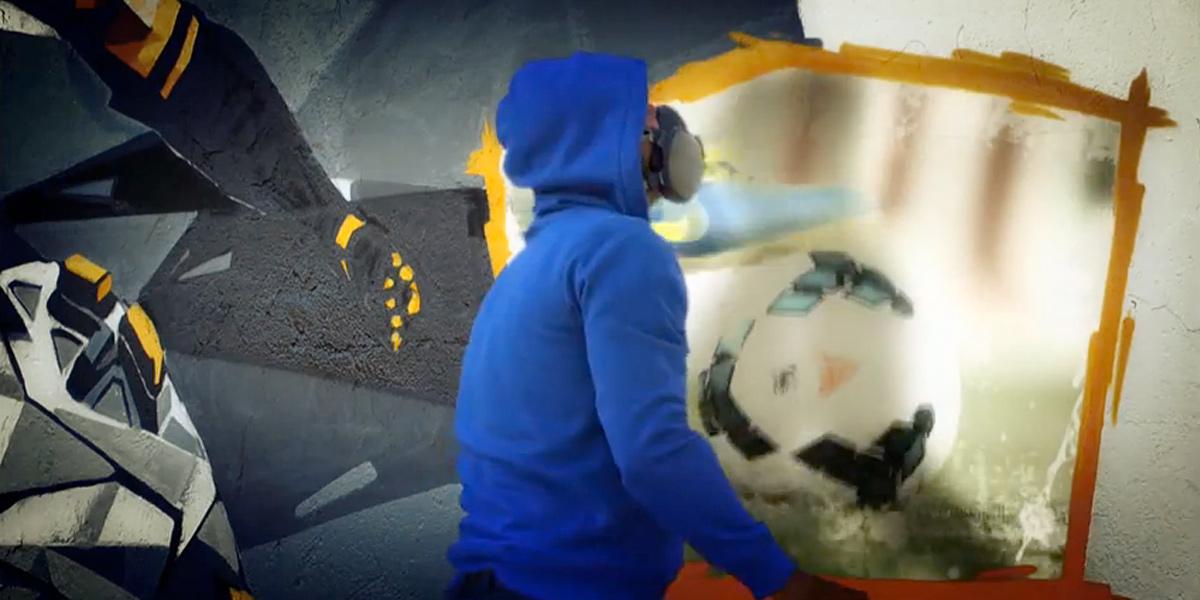 Grafitero pintando la cabecera de El Partidazo del Plus