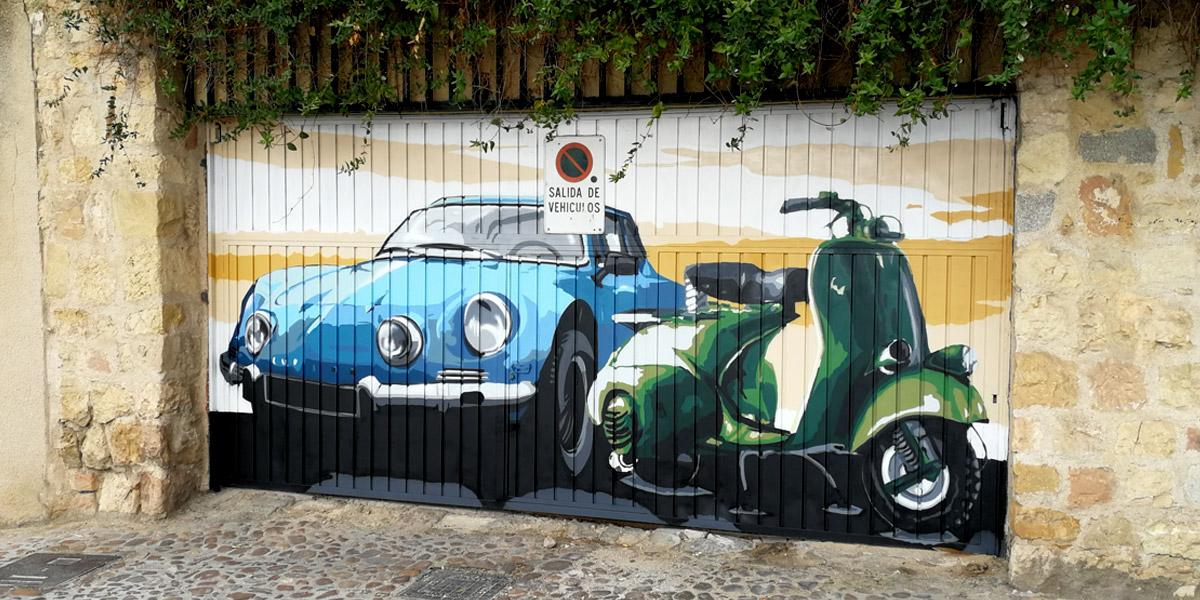 Coche y moto pintando en graffiti en puerta de garaje.