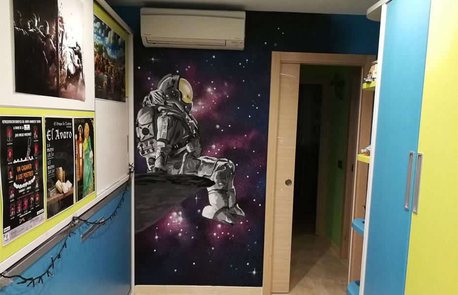 Mural decorativo de astronauta en habitación.