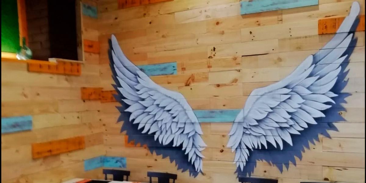 Mural con alas de ángel en bar.