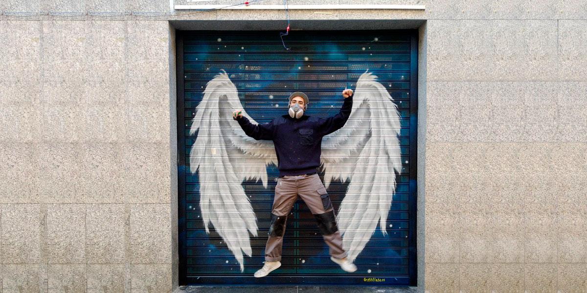 Posando con graffiti de alas en Madrid.