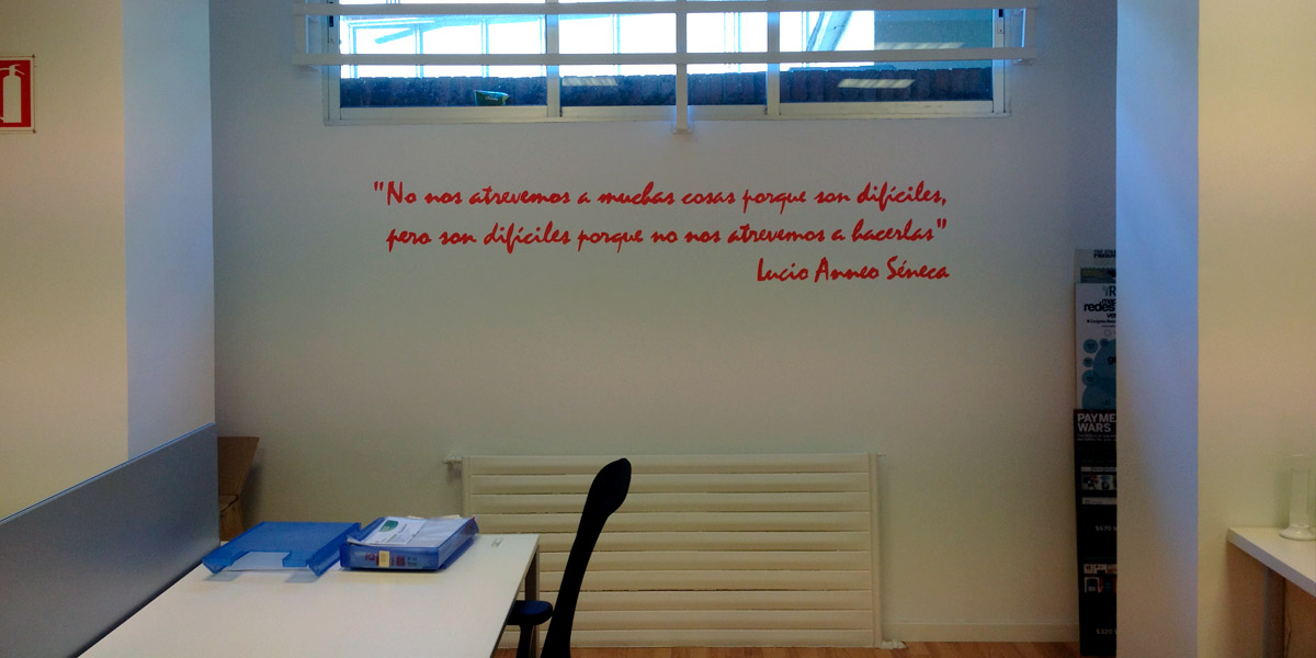 Frase motivadora pintada a mano en oficina.